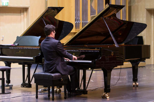 Adult man playing grand piano on stage