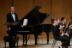Concert classical pianist with orchestra on stage